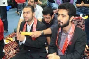 """Foto orang syi`ah yang mengenakan kalung merah bertuliskan arab terjemahannya : """" Aisyah di Neraka """"."""