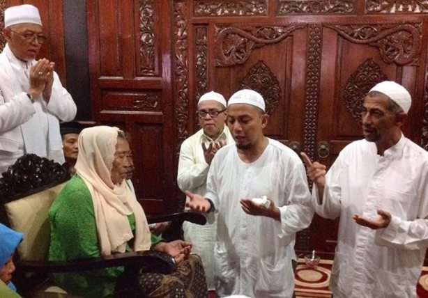 KH. Muhammad Arifin Ilham membimbing nenek Rubiah yang masuk Islam di hadapan ribuan jama'ah